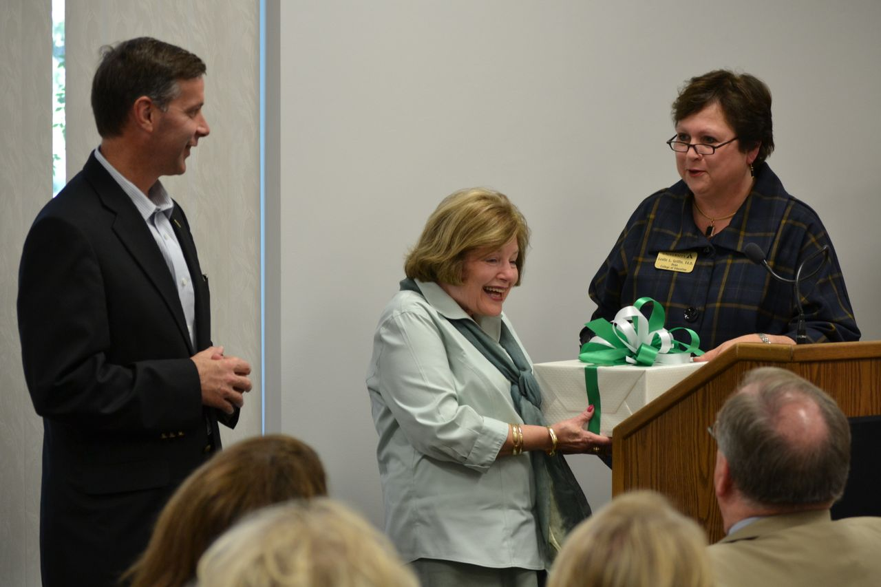PHOTO:  Dr. Janie Allen-Bradey (center) receives a gift of hand carved bookends from Delta State Foundation Executive Director Keith Fulcher (left) and Dean of the College of Arts and Sciences Dr. Leslie Griffin.
