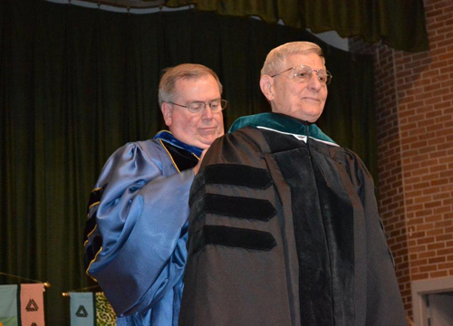 Delta State University President Dr. John Hilpert (back) hoods retired State Senator and Delta State alumnus Bob M. Dearing, bestowing one of the university's highest honors – an honorary Doctor of Public Service degree.
